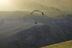 La gente che progetta su un paracadute contro il contesto di belle montagne e del tramonto Fotografia Stock