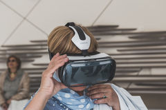 La gente che prova cuffia avricolare 3D all'Expo 2015 a Milano, Italia Immagine Stock