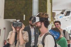La gente che prova cuffia avricolare 3D all'Expo 2015 a Milano, Italia Fotografia Stock Libera da Diritti