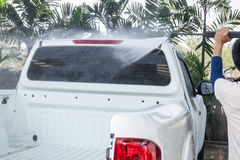 La gente che pulisce e che lava automobile con la rondella ad alta pressione immagini stock libere da diritti