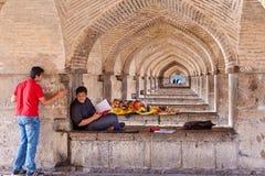 La gente che riposa ai sedili di pietra sotto il ponte di Khaju, Ispahan, Iran Fotografie Stock