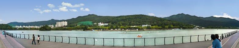 La gente che riposa dal lago nel parco della città con le montagne dentro indietro immagine stock