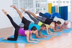 La gente che si esercita sulle stuoie di forma fisica alla palestra Fotografia Stock