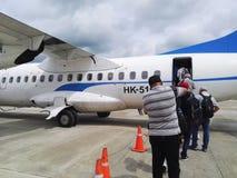 La gente che si imbarca su un piccolo aereo di elica dalla pista di un aeroporto tropicale Fotografia Stock