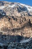 La gente che si leva in piedi prima della roccia enorme in montagna Fotografia Stock Libera da Diritti