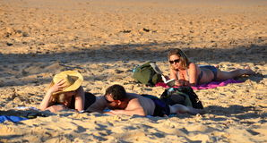 La gente che si rilassa sulla spiaggia Una donna che legge un libro nei precedenti Una coppia che parla nella f Fotografie Stock