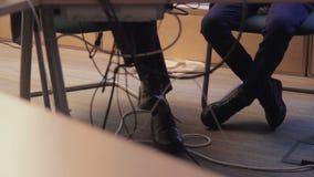 La gente che si siede nella fine interna della Camera sulla gamba, sul piede, sulla scarpa e sulle corde archivi video