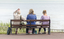 La gente che si siede su un banco Immagini Stock