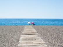 La gente che si siede sulla spiaggia davanti al mare Immagine Stock Libera da Diritti
