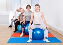La gente che si siede sulle palle di forma fisica nella classe di esercizio Fotografie Stock Libere da Diritti