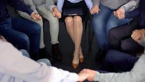 La gente che si tiene per mano alla sessione di terapia, all'assistenza di depressione, alla riabilitazione ed alla salute immagine stock
