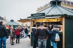 La gente che socializza dentro il Natale ed il mercato del nuovo anno al palazzo di Schonbrunn, Vienna, Austria fotografia stock libera da diritti