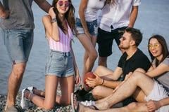 La gente che spende insieme tempo piacevole mentre sedendosi sulla birra divertiresi e di bevanda della spiaggia, immagini stock