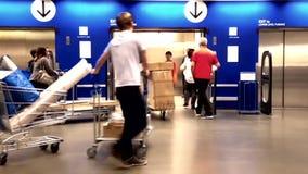 La gente che spinge la loro mobilia sul carrello verso l'elevatore archivi video