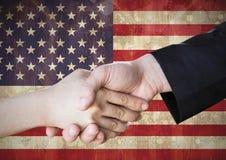 La gente che stringe insieme le loro mani contro la bandiera americana Fotografie Stock Libere da Diritti