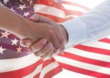 la gente che stringe le loro mani contro la bandiera americana Immagini Stock