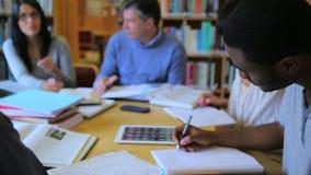 La gente che studia come gruppo in biblioteca stock footage