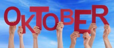 La gente che tiene la parola Oktober significa il cielo blu di ottobre Immagini Stock