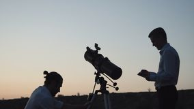La gente che utilizza telescopio nell'alba video d archivio