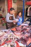 La gente che vende e che compra in un mercato tradizionale del centro di Kunming immagine stock