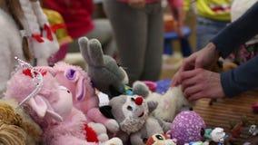 La gente che vende i giocattoli molli alla vendita di garage di carità, alzante i fondi per aiutare i bambini video d archivio