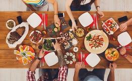 La gente come comidas sanas en el partido de cena festivo de la tabla Fotos de archivo