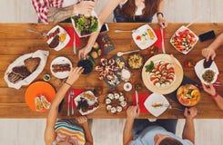 La gente come comidas sanas en el partido de cena festivo de la tabla Imágenes de archivo libres de regalías