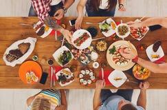 La gente come comidas sanas en el partido de cena festivo de la tabla Foto de archivo