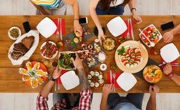 La gente come comidas sanas en el partido de cena festivo de la tabla Fotografía de archivo