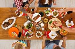 La gente come comidas sanas en el partido de cena festivo de la tabla Foto de archivo libre de regalías