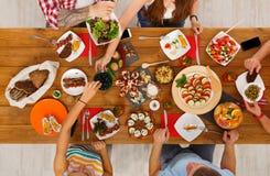 La gente come comidas sanas en el partido de cena festivo de la tabla Fotos de archivo libres de regalías