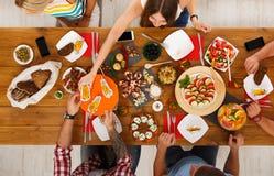 La gente come comidas sanas en el partido de cena festivo de la tabla Imagen de archivo libre de regalías