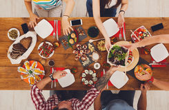 La gente come comidas sanas en el partido de cena servido de la tabla Foto de archivo libre de regalías
