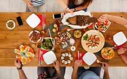 La gente come comidas sanas en el partido de cena servido de la tabla Imágenes de archivo libres de regalías