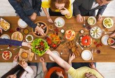 La gente come comidas sanas en el partido de cena servido de la tabla Imagen de archivo libre de regalías