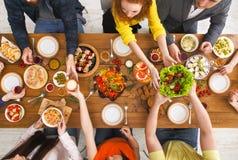 La gente come comidas sanas en el partido de cena servido de la tabla Fotografía de archivo libre de regalías