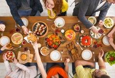 La gente come comidas sanas en el partido de cena servido de la tabla Fotografía de archivo