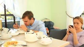 La gente come en un café, un hombre come haber descontentado, miradas de una mujer en su teléfono Conflicto de relaciones almacen de metraje de vídeo