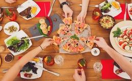 La gente come la pizza en el partido de cena festivo de la tabla Imágenes de archivo libres de regalías