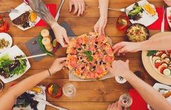 La gente come la pizza en el partido de cena festivo de la tabla Fotos de archivo libres de regalías