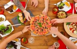 La gente come la pizza en el partido de cena festivo de la tabla Fotografía de archivo