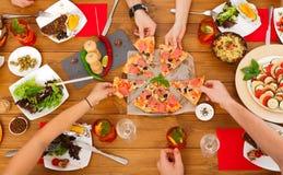 La gente come la pizza en el partido de cena festivo de la tabla Imagenes de archivo