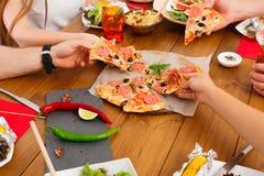 La gente come la pizza en el partido de cena festivo de la tabla Imagen de archivo