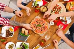 La gente come la pizza en el partido de cena festivo de la tabla Foto de archivo libre de regalías