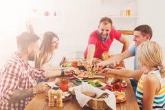 La gente come la pizza en el partido de cena festivo de la tabla Imagen de archivo libre de regalías