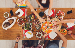 La gente come maíz asado a la parrilla en el partido de cena servido de la tabla Foto de archivo