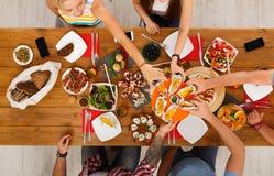 La gente come maíz asado a la parrilla en el partido de cena servido de la tabla Foto de archivo libre de regalías