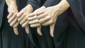 La gente con gli abiti neri di graduazione si batte giù Fotografie Stock