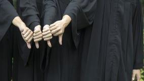 La gente con gli abiti neri di graduazione si batte giù Fotografie Stock Libere da Diritti