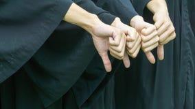 La gente con gli abiti neri di graduazione si batte giù Fotografia Stock Libera da Diritti